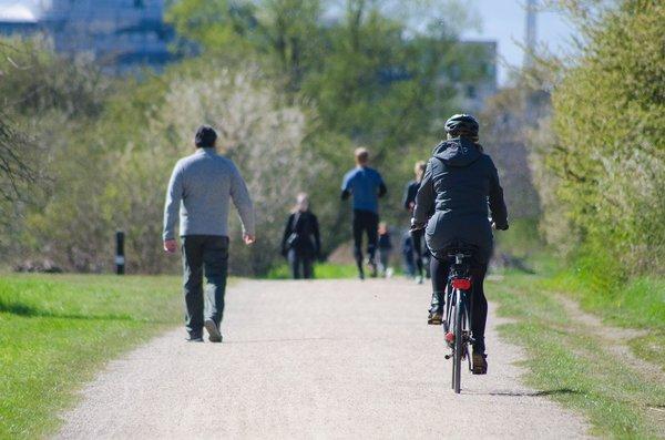 Velofahrer und Fussgänger in einem Park.