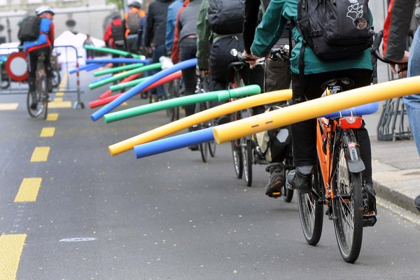 Radfahrer demonstrieren mit Badenudeln auf dem Gepäckträger für mehr Abstand beim Überholen.